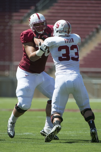 April 12, 2014; Stanford, CA, USA; Stanford Cardinal offensive tackle Andrus Peat (70, left) blocks outside linebacker Mike Tyler (33) during the spring game at Stanford Stadium. Mandatory Credit: Kyle Terada-USA TODAY Sports