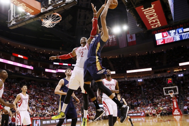 Apr 12, 2014; Houston, TX, USA; New Orleans Pelicans center Alexis Ajinca (right) shoots as Houston Rockets center Dwight Howard (12)  defends during the first half at Toyota Center. Mandatory Credit: Soobum Im-USA TODAY Sports