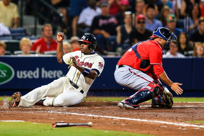 Apr 12, 2014; Atlanta, GA, USA; Atlanta Braves left fielder Justin Upton (8) slides into home to score before the tag by Washington Nationals catcher Sandy Leon (41) in the fifth inning at Turner Field. Mandatory Credit: Daniel Shirey-USA TODAY Sports
