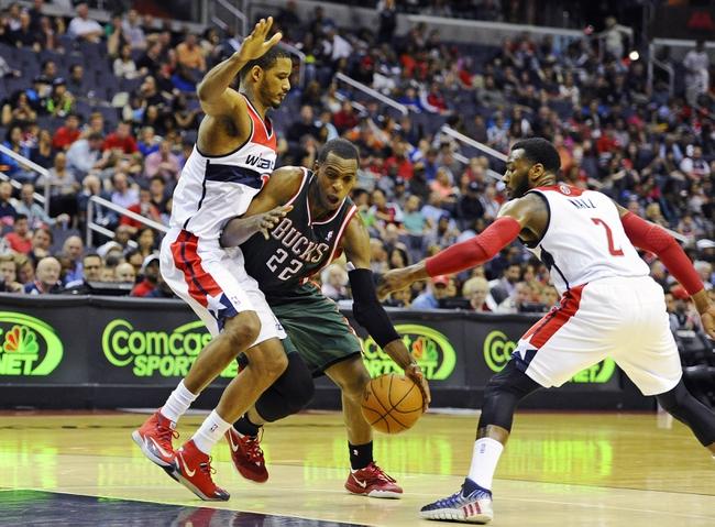 Apr 12, 2014; Washington, DC, USA; Milwaukee Bucks power forward Khris Middleton (22) is fouled by Washington Wizards small forward Trevor Ariza (1) during the second half at Verizon Center. The Wizards won 104-91. Mandatory Credit: Brad Mills-USA TODAY Sports