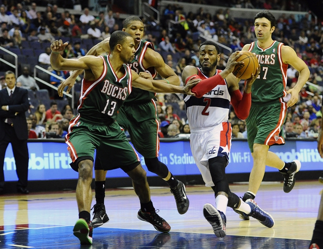 Apr 12, 2014; Washington, DC, USA; Washington Wizards point guard John Wall (2) drives to the basket as Milwaukee Bucks point guard Ramon Sessions (13) and shooting guard Giannis Antetokounmpo (34) and center Zaza Pachulia (27) defend during the first half at Verizon Center. Mandatory Credit: Brad Mills-USA TODAY Sports