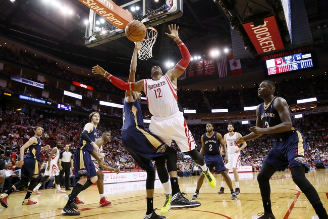Apr 12, 2014; Houston, TX, USA; Houston Rockets center Dwight Howard (12) is fouled while shooting against New Orleans Pelicans center Alexis Ajinca (left) during the second half at Toyota Center. The Rockets won 111-104. Mandatory Credit: Soobum Im-USA TODAY Sports