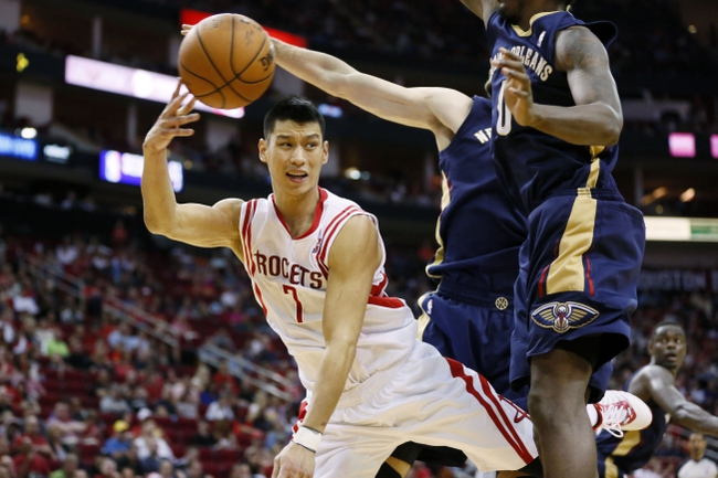 Apr 12, 2014; Houston, TX, USA; Houston Rockets guard Jeremy Lin (7) passes the ball under the basket during the second half against the New Orleans Pelicans at Toyota Center. The Rockets won 111-104. Mandatory Credit: Soobum Im-USA TODAY Sports