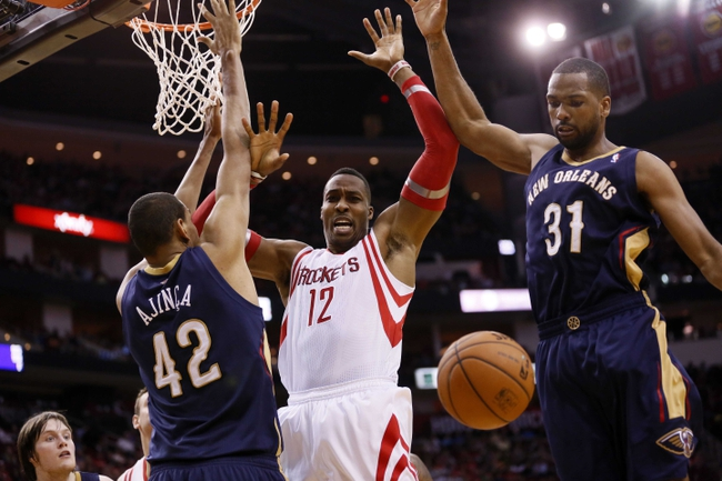 Apr 12, 2014; Houston, TX, USA; Houston Rockets center Dwight Howard (12) battles for a loose ball with New Orleans Pelicans center Alexis Ajinca (42) and forward James Southerland (31) during the second half at Toyota Center. The Rockets won 111-104. Mandatory Credit: Soobum Im-USA TODAY Sports
