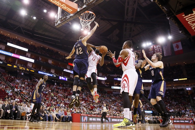 Apr 12, 2014; Houston, TX, USA; Houston Rockets guard James Harden (13) drives to the basket under pressure from New Orleans Pelicans center Alexis Ajinca (42) during the second half at Toyota Center. The Rockets won 111-104. Mandatory Credit: Soobum Im-USA TODAY Sports