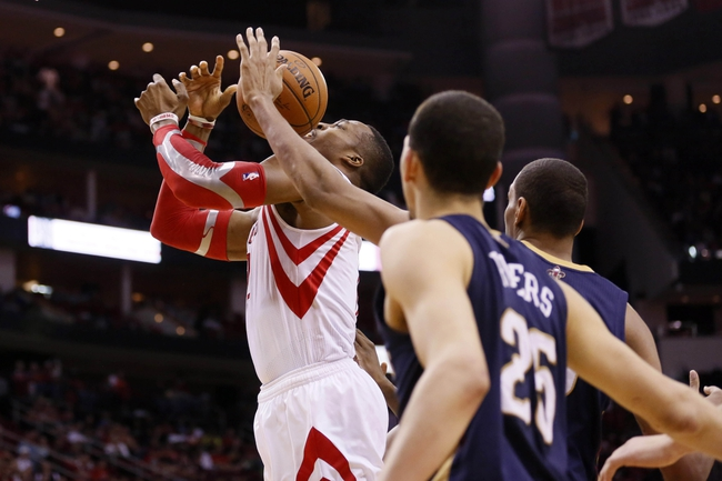 Apr 12, 2014; Houston, TX, USA; Houston Rockets center Dwight Howard (left) gets fouled while shooting against New Orleans Pelicans center Alexis Ajinca (right) during the second half at Toyota Center. The Rockets won 111-104. Mandatory Credit: Soobum Im-USA TODAY Sports