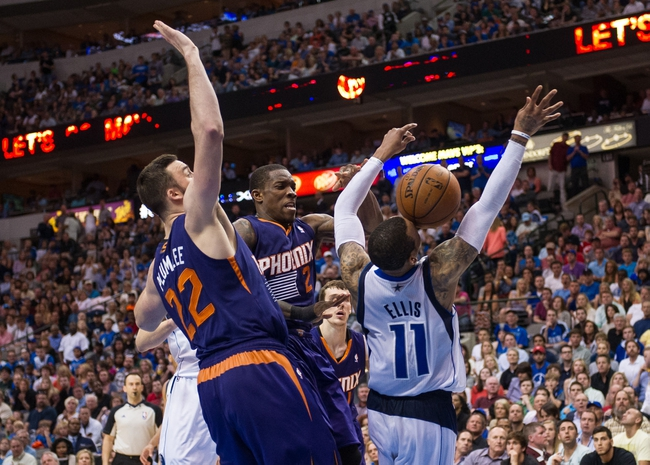 Apr 12, 2014; Dallas, TX, USA; Dallas Mavericks guard Monta Ellis (11) is fouled as he drives to the basket past Phoenix Suns center Miles Plumlee (22) and guard Eric Bledsoe (2) during the second half at the American Airlines Center. The Mavericks defeated the Suns 101-98 and clinched a spot in the NBA playoffs. Mandatory Credit: Jerome Miron-USA TODAY Sports