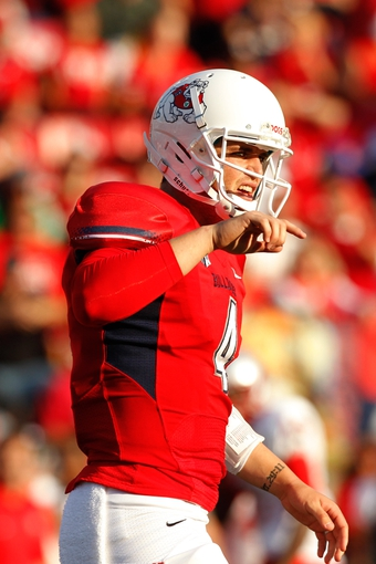Nov 23, 2013; Fresno, CA, USA; Fresno State Bulldogs quarterback Derek Carr (4) stands behind the line of scrimmage against the New Mexico Lobos in the third quarter at Bulldog Stadium. The Bulldogs defeated the Lobos 69-28. Mandatory Credit: Cary Edmondson-USA TODAY Sports