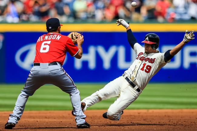 Apr 13, 2014; Atlanta, GA, USA; Atlanta Braves shortstop Andrelton Simmons (19) slides into third on a triple before the tag by Washington Nationals second baseman Anthony Rendon (6) in the first inning at Turner Field. Mandatory Credit: Daniel Shirey-USA TODAY Sports