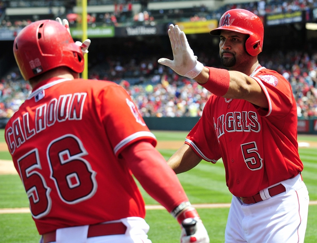 April 13, 2014; Anaheim, CA, USA; Los Angeles Angels designated hitter Albert Pujols (5) is congratulated by right fielder Kole Calhoun (56) after hitting a solo home run in the first inning against the New York Mets at Angel Stadium of Anaheim. Mandatory Credit: Gary A. Vasquez-USA TODAY Sports