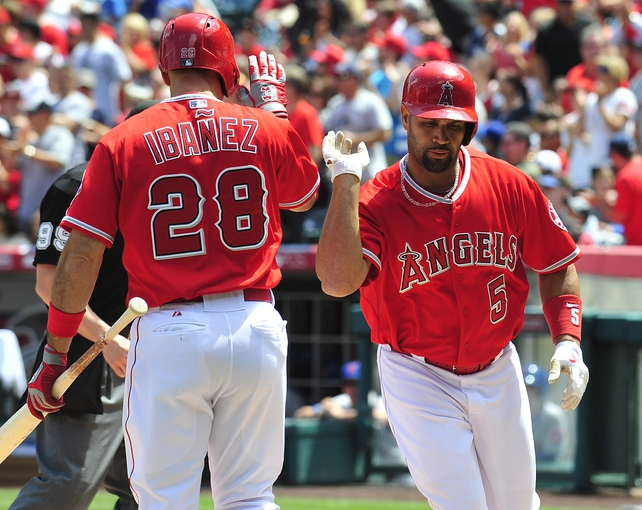 April 13, 2014; Anaheim, CA, USA; Los Angeles Angels designated hitter Albert Pujols (5) is congratulated by first baseman Raul Ibanez (28) after hitting a solo home run in the first inning against the New York Mets at Angel Stadium of Anaheim. Mandatory Credit: Gary A. Vasquez-USA TODAY Sports