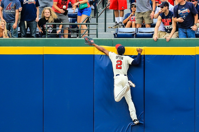 Apr 13, 2014; Atlanta, GA, USA; Atlanta Braves center fielder B.J. Upton (2) climbs the wall in an attempt to catch a Washington Nationals first baseman Adam LaRoche (25) home run in the ninth inning at Turner Field. The Braves won 10-2. Mandatory Credit: Daniel Shirey-USA TODAY Sports