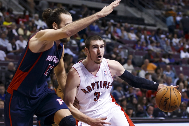 Apr 13, 2014; Auburn Hills, MI, USA; Toronto Raptors guard Nando de Colo (3) dribbles around Detroit Pistons forward Luigi Datome (13) in the second quarter at The Palace of Auburn Hills. Mandatory Credit: Rick Osentoski-USA TODAY Sports