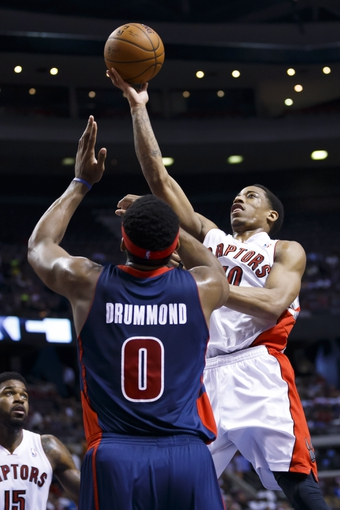 Apr 13, 2014; Auburn Hills, MI, USA; Toronto Raptors guard DeMar DeRozan (10) shoots over Detroit Pistons center Andre Drummond (0) in the second quarter at The Palace of Auburn Hills. Mandatory Credit: Rick Osentoski-USA TODAY Sports