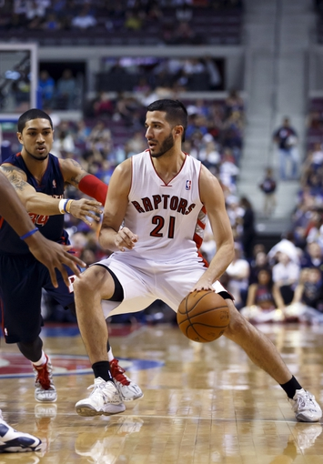 Apr 13, 2014; Auburn Hills, MI, USA; Toronto Raptors guard Greivis Vasquez (21) dribbles around Detroit Pistons guard Peyton Siva (34) in the second quarter at The Palace of Auburn Hills. Mandatory Credit: Rick Osentoski-USA TODAY Sports