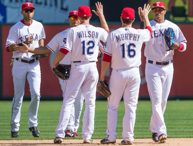 Apr 13, 2014; Arlington, TX, USA; Texas Rangers second baseman Josh Wilson (12) celebrates with teammates after defeating the Houston Astros 1-0 at Globe Life Park. Mandatory Credit: Jerome Miron-USA TODAY Sports