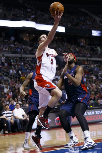 Apr 13, 2014; Auburn Hills, MI, USA; Toronto Raptors guard Nando de Colo (3) goes to the basket on Detroit Pistons center Andre Drummond (0) in the second quarter at The Palace of Auburn Hills. Mandatory Credit: Rick Osentoski-USA TODAY Sports