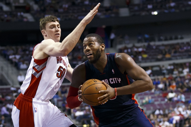 Apr 13, 2014; Auburn Hills, MI, USA; Detroit Pistons forward Greg Monroe (10) dribbles around Toronto Raptors forward Tyler Hansbrough (50) in the fourth quarter at The Palace of Auburn Hills. Mandatory Credit: Rick Osentoski-USA TODAY Sports