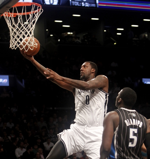 Apr 13, 2014; Brooklyn, NY, USA; Brooklyn Nets center Andray Blatche (0) makes a basket against Orlando Magic guard Victor Oladipo (5) in the second quarter at Barclays Center. Mandatory Credit: Nicole Sweet-USA TODAY Sports