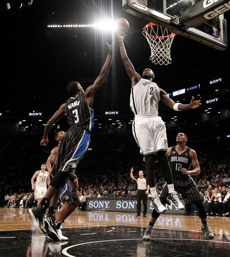 Apr 13, 2014; Brooklyn, NY, USA; Orlando Magic center Dewayne Dedmon (3) blocks a shot put up by Brooklyn Nets forward Kevin Garnett (2) in the fourth quarter at Barclays Center. Nets win 97-88. Mandatory Credit: Nicole Sweet-USA TODAY Sports