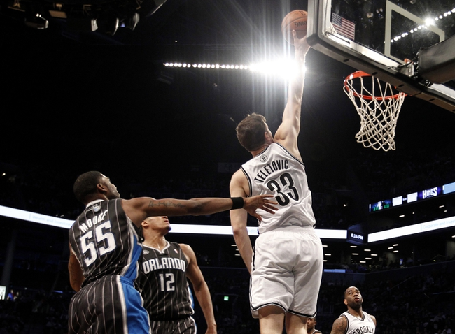 Apr 13, 2014; Brooklyn, NY, USA; Brooklyn Nets forward Mirza Teletovic (33) puts up a shot against Orlando Magic guard E   Twaun Moore (55) and forward Tobias Harris (12) in the fourth quarter at Barclays Center. Nets win 97-88. Mandatory Credit: Nicole Sweet-USA TODAY Sports