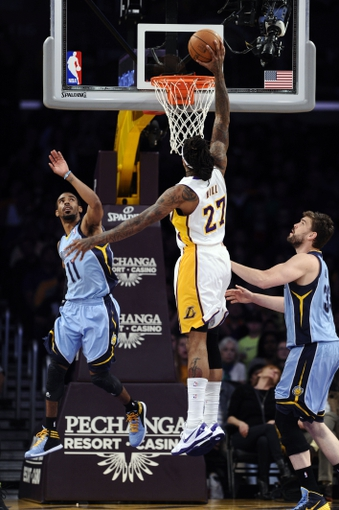 Apr 13, 2014; Los Angeles, CA, USA;  Los Angeles Lakers forward Jordan Hill (27) dunks between Memphis Grizzlies guard Mike Conley (11) and center Marc Gasol (33) during first quarter action at Staples Center. Mandatory Credit: Robert Hanashiro-USA TODAY Sports