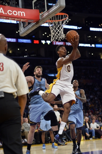 Apr 13, 2014; Los Angeles, CA, USA;  Los Angeles Lakers forward Nick Young (0) puts up a reverse layup past Memphis Grizzlies center Marc Gasol (33) during second half action at Staples Center. Mandatory Credit: Robert Hanashiro-USA TODAY Sports