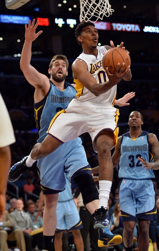 Apr 13, 2014; Los Angeles, CA, USA;  Los Angeles Lakers forward Nick Young (0) shoots past Memphis Grizzlies center Marc Gasol (33) during second half action at Staples Center. Mandatory Credit: Robert Hanashiro-USA TODAY Sports
