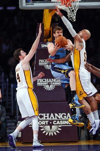 Apr 13, 2014; Los Angeles, CA, USA; Memphis Grizzlies center Marc Gasol (33) tries to put up a shot as he is fouled by Los Angeles Lakers center Robert Sacre (50) during the 4th quarter action at Staples Center. Left is Los Angeles Lakers forward Ryan Kelly (4). Mandatory Credit: Robert Hanashiro-USA TODAY Sports