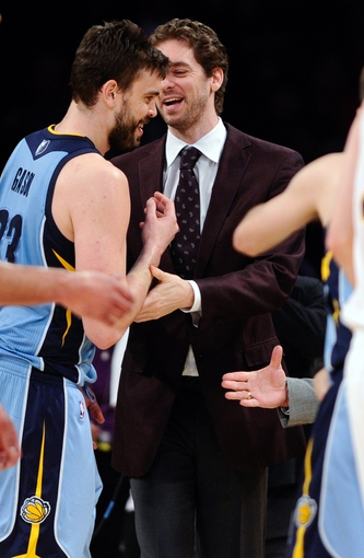 Apr 13, 2014; Los Angeles, CA, USA; Memphis Grizzlies center Marc Gasol (33) greets his brother injured Los Angeles Lakers center Pau Gasol after the Grizzlies 102-90 win at Staples Center. Mandatory Credit: Robert Hanashiro-USA TODAY Sports