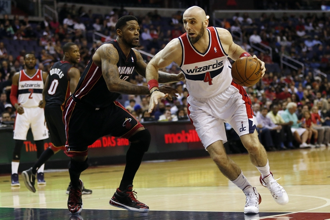 Apr 14, 2014; Washington, DC, USA; Washington Wizards center Marcin Gortat (4) dribbles the ball as Miami Heat forward Udonis Haslem (40) defends in the first quarter at Verizon Center. Mandatory Credit: Geoff Burke-USA TODAY Sports