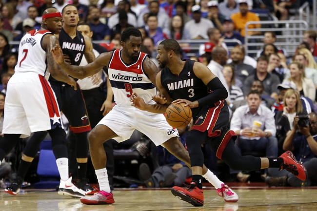 Apr 14, 2014; Washington, DC, USA; Miami Heat guard Dwyane Wade (3) dribbles the ball as Washington Wizards forward Martell Webster (9) defends in the second quarter at Verizon Center. Mandatory Credit: Geoff Burke-USA TODAY Sports