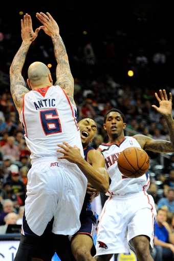 Apr 14, 2014; Atlanta, GA, USA; Charlotte Bobcats guard Gerald Henderson (9) loses the ball after running into Atlanta Hawks center Pero Antic (6) during the first half at Philips Arena. Mandatory Credit: Dale Zanine-USA TODAY Sports