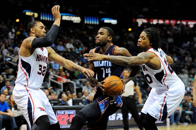 Apr 14, 2014; Atlanta, GA, USA; Charlotte Bobcats forward Michael Kidd-Gilchrist (14) drives past Atlanta Hawks forward Mike Scott (32) and forward Cartier Martin (20) during the first half at Philips Arena. Mandatory Credit: Dale Zanine-USA TODAY Sports