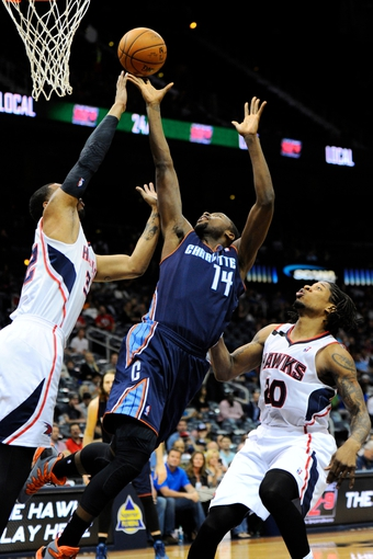 Apr 14, 2014; Atlanta, GA, USA; Charlotte Bobcats forward Michael Kidd-Gilchrist (14) shoots at the basket between Atlanta Hawks forward Mike Scott (32) and forward Cartier Martin (20) during the first half at Philips Arena. Mandatory Credit: Dale Zanine-USA TODAY Sports