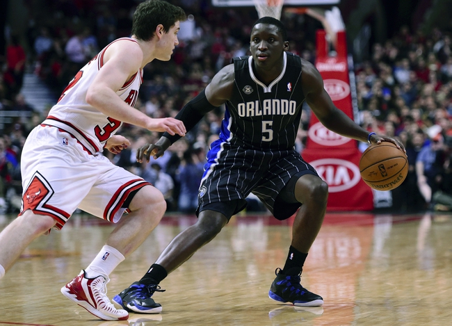 Apr 14, 2014; Chicago, IL, USA; Orlando Magic guard Victor Oladipo (5) dribbles the ball against Chicago Bulls guard Jimmer Fredette (32) during the second quarter at the United Center. Mandatory Credit: Mike DiNovo-USA TODAY Sports