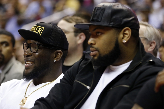 Apr 14, 2014; Washington, DC, USA; Washington Redskins defensive end Brian Orakpo (left) and Redskins offensive tackle Trent Williams (right) watch from court side during the Washington Wizards game against the Miami Heat at Verizon Center. The Wizards won 114-93. Mandatory Credit: Geoff Burke-USA TODAY Sports