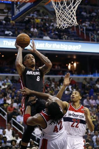 Apr 14, 2014; Washington, DC, USA; Miami Heat forward Michael Beasley (8) shoots the ball as Washington Wizards forward Nene (42) defends in the third quarter at Verizon Center. The Wizards won 114-93. Mandatory Credit: Geoff Burke-USA TODAY Sports