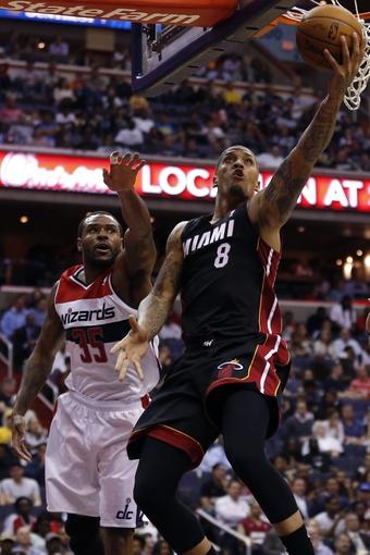 Apr 14, 2014; Washington, DC, USA; Miami Heat forward Michael Beasley (8) shoots the ball as Washington Wizards forward Trevor Booker (35) defends in the fourth quarter at Verizon Center. The Wizards won 114-93. Mandatory Credit: Geoff Burke-USA TODAY Sports