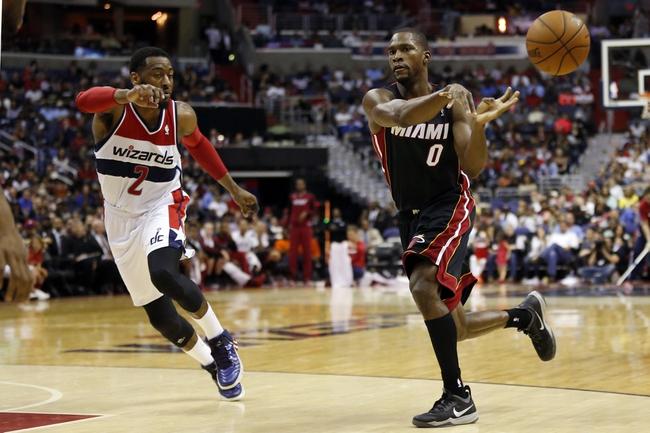 Apr 14, 2014; Washington, DC, USA; Miami Heat guard Toney Douglas (0) passes the ball as Washington Wizards guard John Wall (2) defends in the fourth quarter at Verizon Center. The Wizards won 114-93. Mandatory Credit: Geoff Burke-USA TODAY Sports
