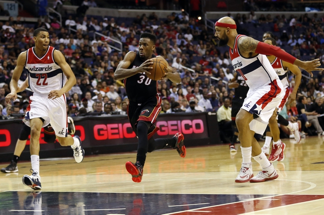 Apr 14, 2014; Washington, DC, USA; Miami Heat guard Norris Cole (30) dribbles the ball between Washington Wizards forward Otto Porter Jr. (22) and Wizards forward Drew Gooden (90) in the fourth quarter at Verizon Center. The Wizards won 114-93. Mandatory Credit: Geoff Burke-USA TODAY Sports