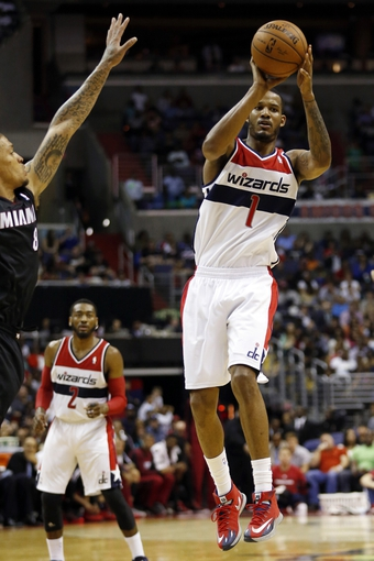 Apr 14, 2014; Washington, DC, USA; Washington Wizards forward Trevor Ariza (1) leaps to pass the ball as Miami Heat forward Michael Beasley (8) defends in the second quarter at Verizon Center. The Wizards won 114-93. Mandatory Credit: Geoff Burke-USA TODAY Sports