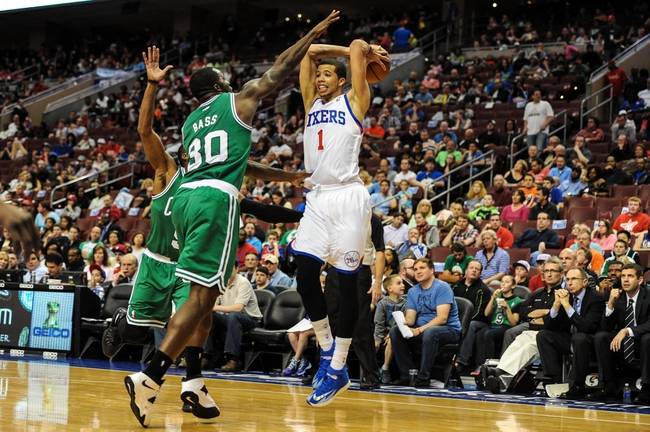 Apr 14, 2014; Philadelphia, PA, USA; Philadelphia 76ers guard Michael Carter-Williams (1) passes as Boston Celtics forward Brandon Bass (30) defends during the third quarter of the game at Wells Fargo Center. Mandatory Credit: John Geliebter-USA TODAY Sports
