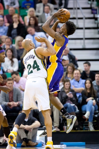 Apr 14, 2014; Salt Lake City, UT, USA; Utah Jazz forward Richard Jefferson (24) fouls Los Angeles Lakers forward Nick Young (0) during the second half at EnergySolutions Arena. The Lakers won 119-104. Mandatory Credit: Russ Isabella-USA TODAY Sports