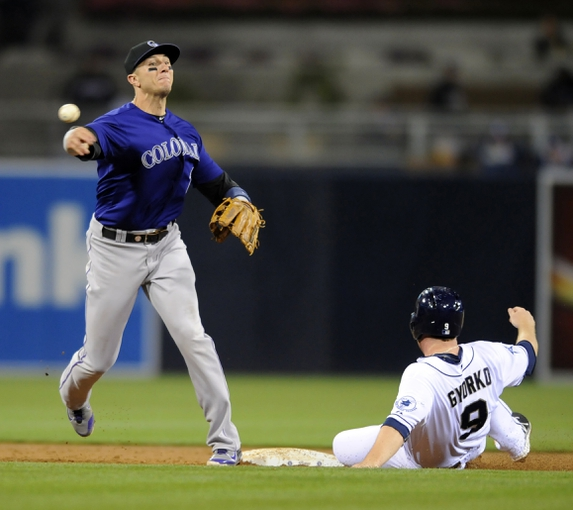 Apr 14, 2014; San Diego, CA, USA; Colorado Rockies shortstop Troy Tulowitzki (2) throws the ball to first ahead of the slide by San Diego Padres second baseman Jedd Gyorko (9) for a double play during the sixth inning at Petco Park. Mandatory Credit: Christopher Hanewinckel-USA TODAY Sports