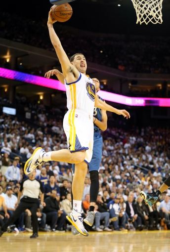 Apr 14, 2014; Oakland, CA, USA; Golden State Warriors guard Klay Thompson (11) goes up for a dunk against Minnesota Timberwolves guard Kevin Martin (23) during the fourth quarter at Oracle Arena. The Golden State Warriors defeated the Minnesota Timberwolves 130-120. Mandatory Credit: Kelley L Cox-USA TODAY Sports