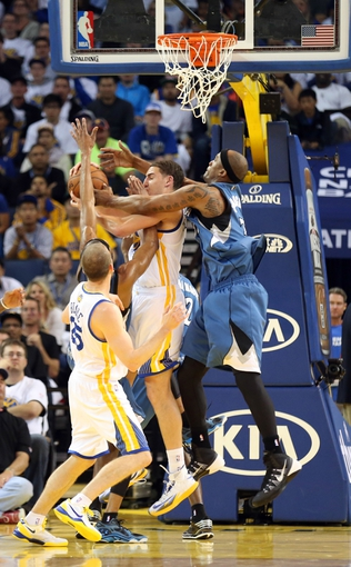 Apr 14, 2014; Oakland, CA, USA; Minnesota Timberwolves forward Dante Cunningham (33) fouls Golden State Warriors guard Klay Thompson (11) above guard Steve Blake (25) during the third quarter at Oracle Arena. The Golden State Warriors defeated the Minnesota Timberwolves 130-120. Mandatory Credit: Kelley L Cox-USA TODAY Sports