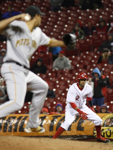 Apr 15, 2014; Cincinnati, OH, USA; Cincinnati Reds center fielder Billy Hamilton, right, watches Pittsburgh Pirates relief pitcher Jeanmar Gomez, left, from first base during the eighth inning at Great American Ball Park. The Reds won 7-5. Mandatory Credit: David Kohl-USA TODAY Sports