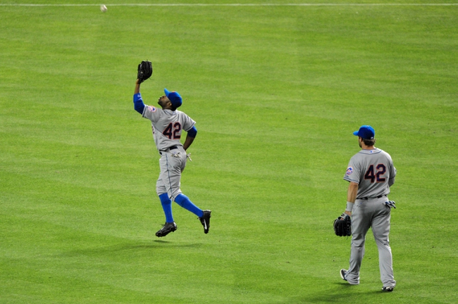 Apr 15, 2014; Phoenix, AZ, USA; New York Mets left fielder Eric Young Jr. (left) catches a fly ball hit by Arizona Diamondbacks catcher Miguel Montero (not pictured) as center fielder Krk Nieuwenhuis (right) looks on during the fourth inning at Chase Field. Mandatory Credit: Matt Kartozian-USA TODAY Sports