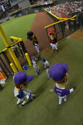 Apr 15, 2014; Phoenix, AZ, USA; Arizona Diamondbacks legend character of Luis Gonzalez (left) wrestles with a member of the New York Mets bullpen staff as players and legends watch during the sixth inning at Chase Field. Mandatory Credit: Matt Kartozian-USA TODAY Sports